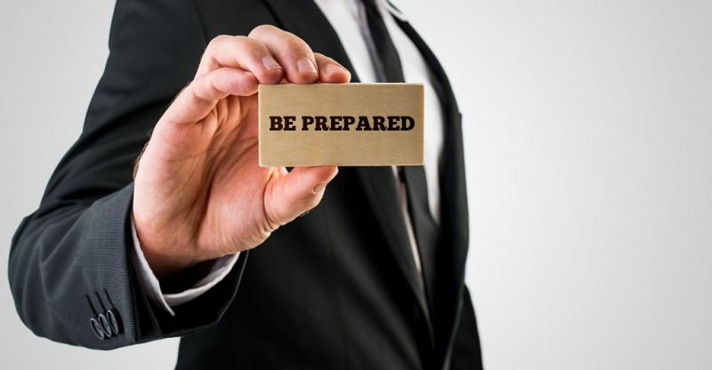 Businessman holding a card saying - Be Prepared - in his hand in a conceptual image of planning and strategy.